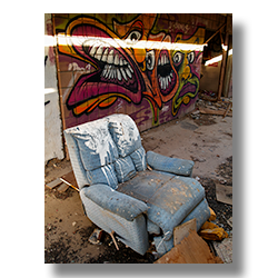 Photo of a blue reclining chair in front of a wall of graffitti by Jim Witkowski.