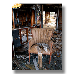 Photo of a brown side chair in a distroyed trailer home by Jm Witkowski.