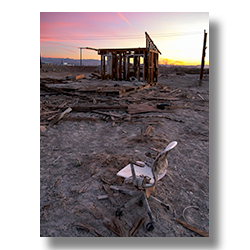 Photo of an office chair at sunrise among the ruins of Bombay Beach by Jim Witkowski.