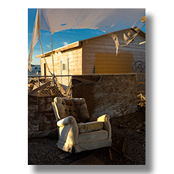 Photo of a rocking easy chair by a shed in Bombay Beach, California by Jim Witkowski